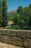 Stone breastwork from the Roman bridge in Portagem. Stone breastwork from the Roman bridge and Marvao village on top of crag in the background, on sunny day at stock image