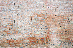 Stone and brick monastery wall with crenels within Stock Photos