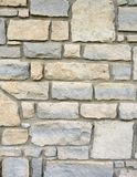 Stone brick wall exterior with mortar. Exterior wall of a stone brick building with neutral shades of gray and sandy brown beige. Mortar is gray. Natural edges Royalty Free Stock Photography