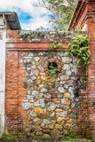 Stone and brick wall between to abandond structures. With circular opening in the center Stock Photography
