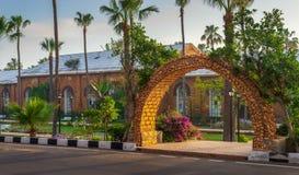 Stone bricks orange arch revealing the royal plant nursery at Montazah public park with trees and palms, Alexandria, Egypt. Stone bricks orange arch revealing Stock Photo