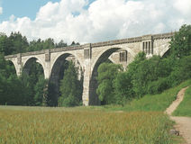 Stone bridge. A railway bridge, that was never used for railway after being built. A field in front of it Stock Photos