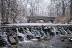 Stone Bridge. Snow Covered Trees Framing A Stone Bridge And Waterfall During Winter In The Park, Sharon Woods, Southwestern Ohio Royalty Free Stock Photos