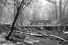 Stone Bridge. Snow Covered Trees Framing A Stone Bridge And Waterfall During Winter In The Park, Black And White, Sharon Woods, Southwestern Ohio, USA Royalty Free Stock Images