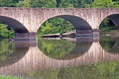 Stone Bridge. A stone arched bridge over a river with reflection royalty free stock photography