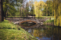 Stone bridge across the lake in a park in spring Royalty Free Stock Image