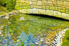 Stone bridge across the river. With clear water Stock Images