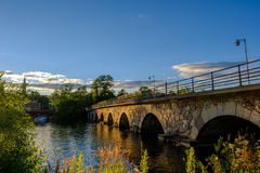 Stone bridge across the water. In the evening sun Royalty Free Stock Photography