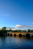 Stone bridge across the water. In the evening sun Stock Photos