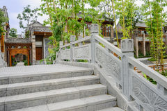 Stone bridge with bass-relief before Chinese traditional buildin Stock Photo