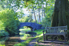 Stone bridge, bench by oak tree by English canal in a forest Stock Photos