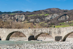 Stone bridge in Bobbio. Stone bridge over the river Trebbia in Bobbio with hills in the background Royalty Free Stock Photography
