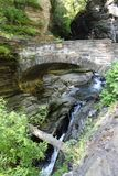 Stone bridge and cascades at Watkins Glen State Park. Cascade falls and steep walls of the gorge. View from the walking trail stock photo