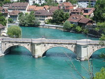 Stone bridge in city of Bern. Stone bridge over clean alpine Aare river with clean water and swiss historical houses on bank in city of BERN BERNE in SWITZERLAND Stock Image