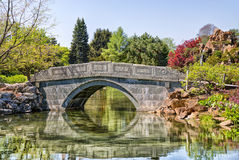 Stone bridge crosses a pond Stock Photos