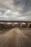 Stone bridge and dirt road Stock Images