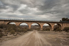 Stone bridge and dirt road Stock Image