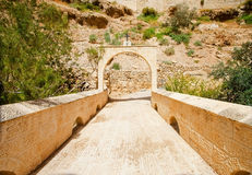 Bridge to Holiness. Stone bridge and a gate archway with Greek Orthodox Church symbol Royalty Free Stock Images