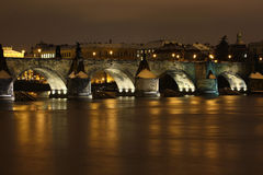 Stone bridge at night. Classic old arched stone bridge over a river at night.  Prague Stock Photography