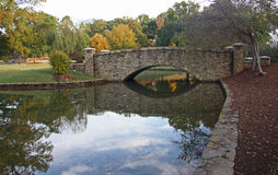 Stone Bridge Over Calm Pond Stock Image