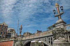 Stone bridge over canal decorated by sculpture of ship`s bow and elegant light post in Amsterdam. The city is famous for its huge cultural activity, graceful Stock Images