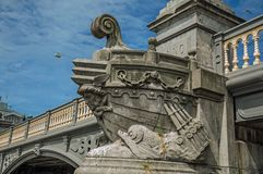 Stone bridge over canal decorated by sculpture of ship`s bow and sunny blue sky in Amsterdam. The city is famous for its huge cultural activity, graceful Royalty Free Stock Image