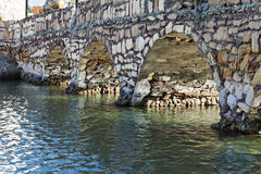 Stone bridge over a close-up perspective river Royalty Free Stock Photography