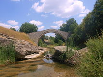 Stone bridge over creek. A view of an old stone bridge walkway over a small creek royalty free stock images