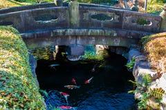 Stone Bridge. A stone bridge over a creek full of colorful koi fish Royalty Free Stock Photo