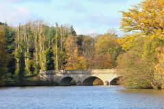 Stone bridge over a lake in the Autumn sunshine with tree leaves. Turned orange and yellow in the fall Stock Images