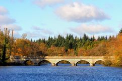Stone bridge over a lake in the Autumn sunshine with tree leaves. Turned orange and yellow in the fall Stock Image