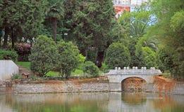 Stone bridge over pond in park of Kunming Stock Image