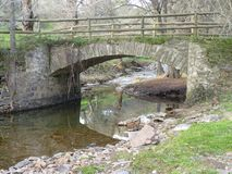 Stone bridge over river. In the forest Stock Images