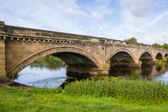 Stone Bridge over The River Trent between Repton and Willington. Derbyshire. Showing the river, cloudy sunny blue sky, green folage foreground, reflection of Royalty Free Stock Photography