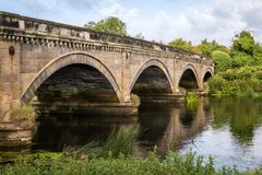 Stone Bridge over The River Trent between Repton and Willington. Derbyshire. Showing the river, cloudy sunny blue sky, green folage foreground, reflection of Royalty Free Stock Images