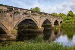 Stone Bridge over The River Trent between Repton and Willington. Derbyshire. Showing the river, cloudy sunny blue sky, green folage foreground, reflection of Royalty Free Stock Image