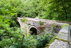 Stone bridge over the small river, Wales, UK. Ancient arch stone bridge over a small river, Wales, UK Stock Photo