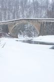 Stone Bridge over Stream in Winter Royalty Free Stock Image