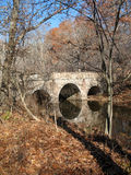 Stone Bridge - Pennsylvania. Stone arch bridge is reflected in slow moving stream on a sunny autumn day. Washington Crossing State Park, Pennsylvania, USA Royalty Free Stock Photos