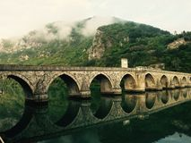 Stone bridge reflecting in river  Royalty Free Stock Photos