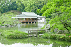 Stone bridge with reflection and pavilion building in zen garden Stock Images