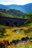 Stone bridge with river and hills. A stone bridge running through a nature scene Stock Photos