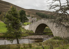 Stone bridge in Scotland. This picture shows a stone bridge in Scotland. There are some old-fashioned buildings visible in the background as well Royalty Free Stock Photography