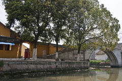 River side. A stone bridge, a small temple and a row of trees at the river side Royalty Free Stock Photos
