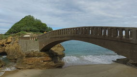 Stone bridge to the islet Rocher Du Basta 09. Dolly Truck Left side away from the bridge on the islet called Rocher du Basta, a beautiful cloudy day on the beach stock footage