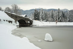 Stone bridge in winter with frozen lake Stock Image
