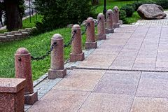 Brown old pillars with chains on the sidewalk near the green lawn with grass Royalty Free Stock Images
