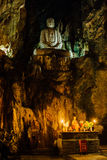 Stone Buddha inside the cave temple above an altar with candles Royalty Free Stock Image