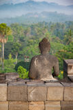 Stone Buddha looking to the jungle from Borobudur temple, Indonesia Royalty Free Stock Images
