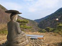 Stone buddha statue facing mountains on sunny day Stock Image